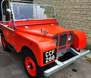 Red early Land Rover with hand painted number plates